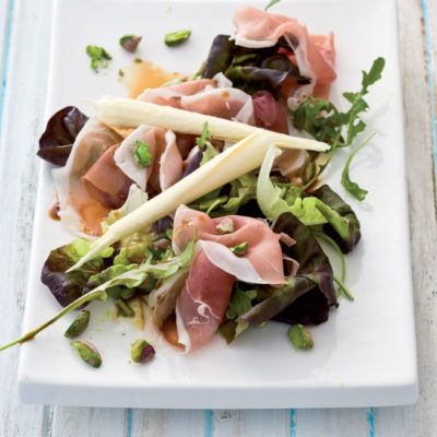 Elegant Parma ham and pistachio salad topped with white chocolate curls