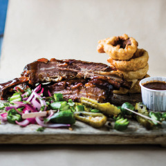 Smoked giant beef ribs with beer-battered onion rings and jalapeno pickle
