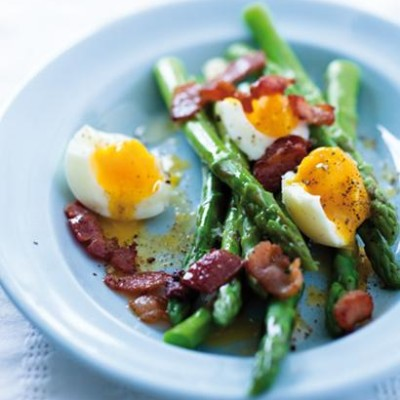 Asparagus spears dressed in salty butter with soft-boiled eggs
