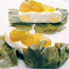 Brie and watermelon preserve wrapped in vine leaves