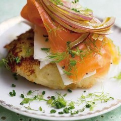 Crispy potato cakes draped with salmon and red onion slivers