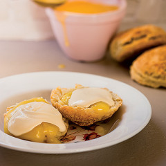 Golden scones topped with thick lemon curd and clotted cream