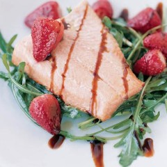 Grilled salmon trout and strawberries with balsamic on wild rocket