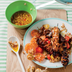 Kebabs with tomato salad and roasted garlic and peanut dressing