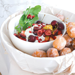 Piles of frosted mini doughnuts with fresh berries and creamy lemon-curd yoghurt
