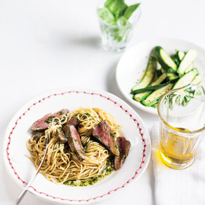 Rare grilled venison steaks with basil oil on pasta