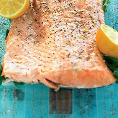 Roast citrus-salted salmon and lemons served with baked potato in cream