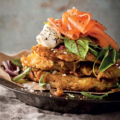 Potato rostis topped with salad greens, salmon and crème fraîche