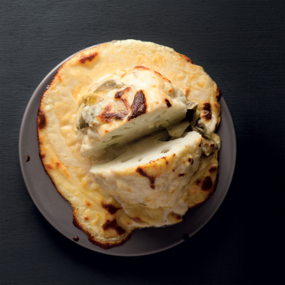 Whole baked cauliflower with cheese sauce