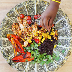 Black jollof rice with roast chicken, grilled pimentos and chargrilled corn