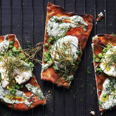 Poached egg pizza with smashed peas, charred leeks and dill mayo