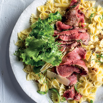 Seared beef carpaccio on lemon-oil and anchovy-dressed pasta with parmesan and greens