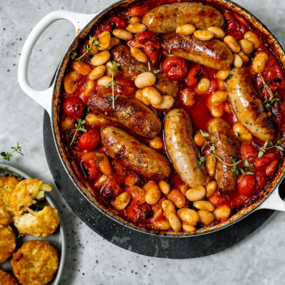 Sausage, butter bean and tomato tray bake with crispy röstis