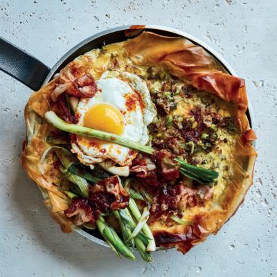 Leek-and-pancetta skillet breakfast tart with crispy harissa-fried eggs